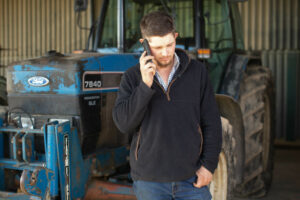 Male farmer in front of a blue tractor holding his mobile phone to his ear with the other hand in his pocket.