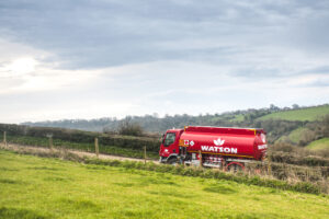 Watson red lorry driving on a road with fields either side.
