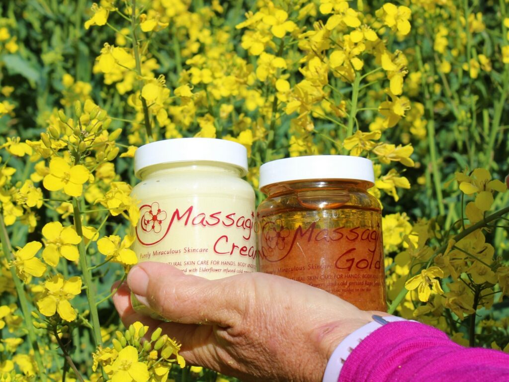 Bright yellow rapeseed flowers, a women's hand holding Massagical products