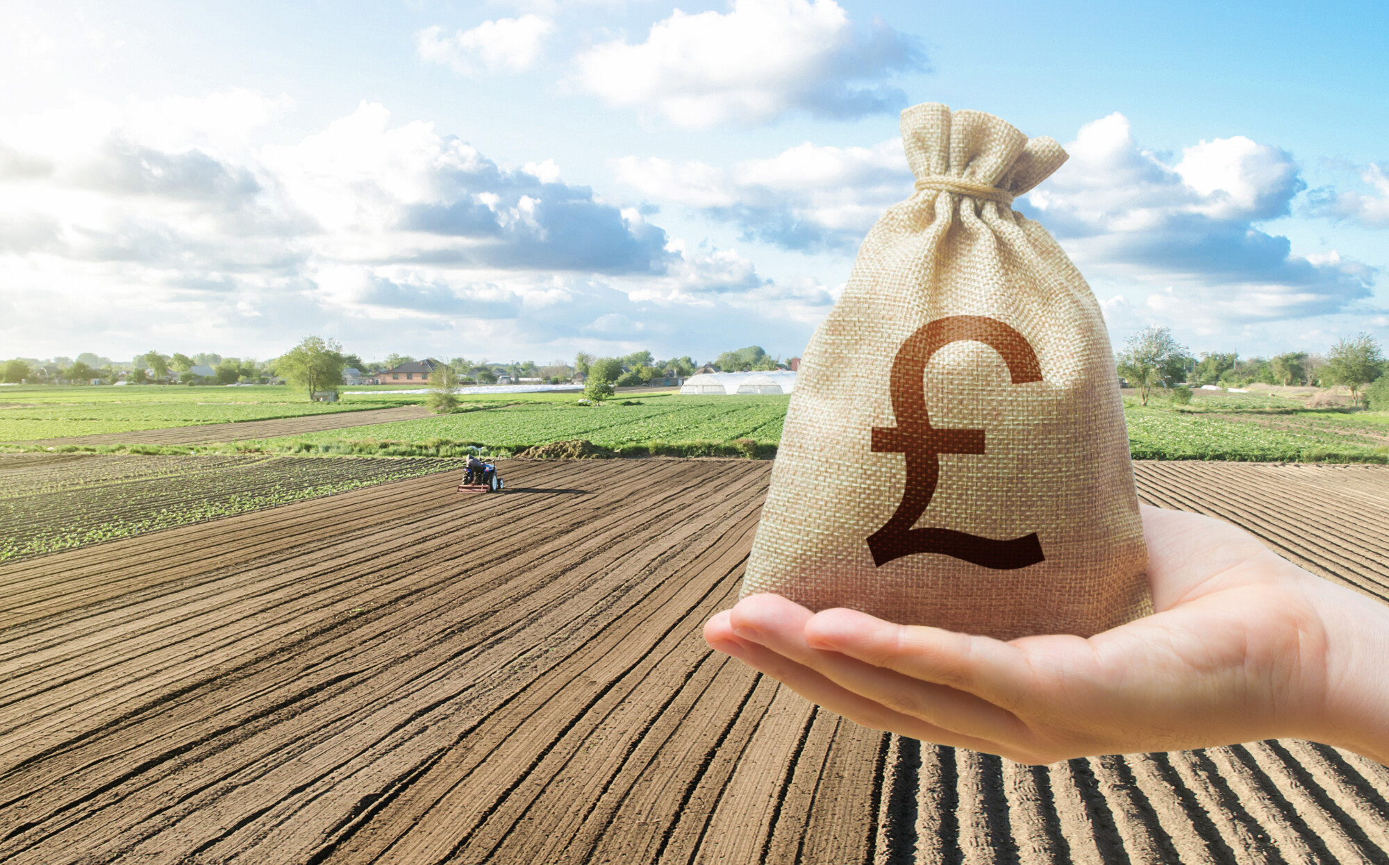 Hand with british pound sterling and a farmer on a tractor works on farm field. Financial support, subsidies for agriculture.