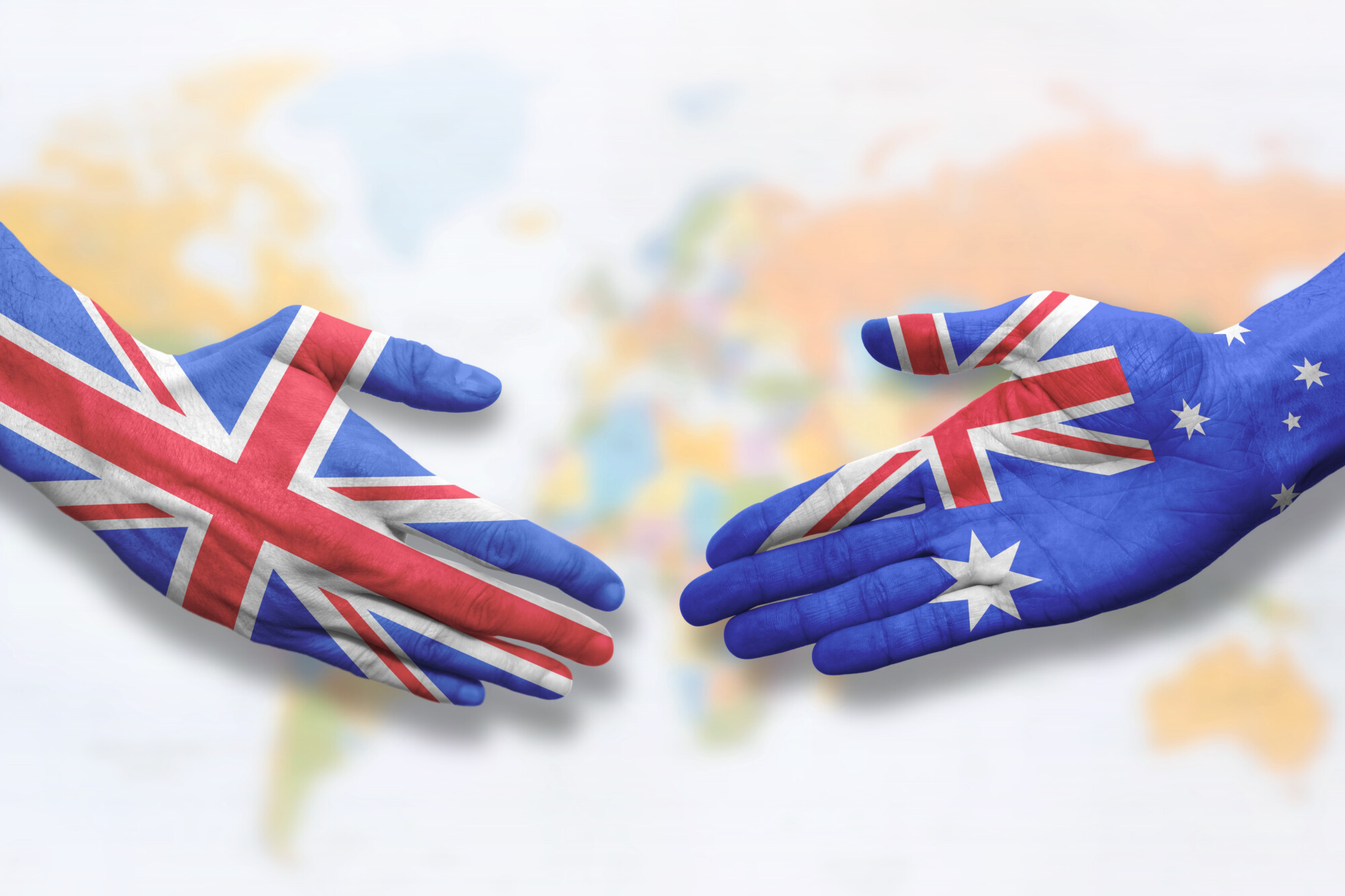 painted hands about to shake - one painted with a Great Britain flag and the other with an Australian flag representing the UK-Australia trade deal