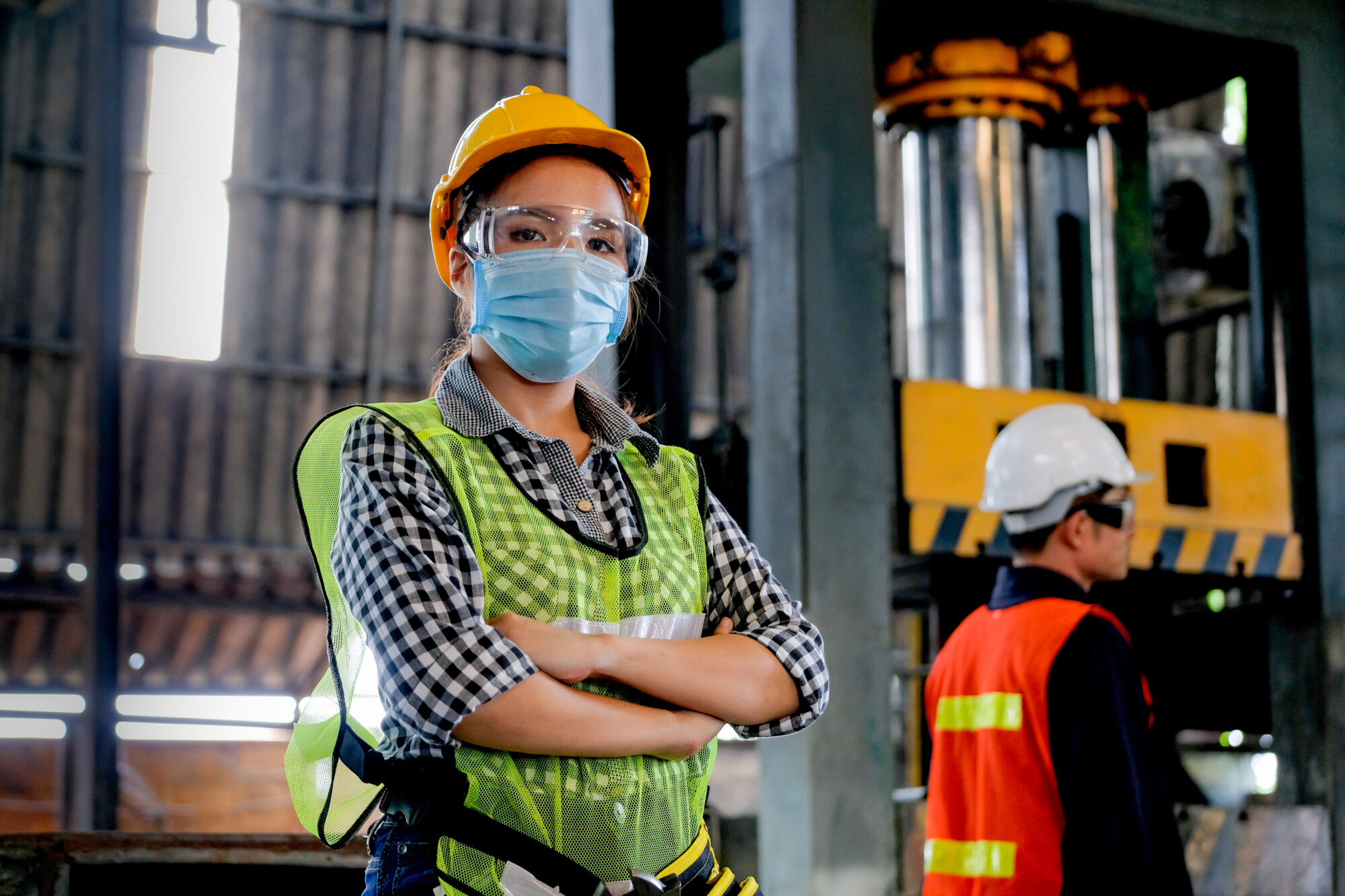 UK food Factory woman worker or technician with hygienic mask stand with confident action with her co-worker engineer in workplace during concern about covid pandemic in people affect industrial business.